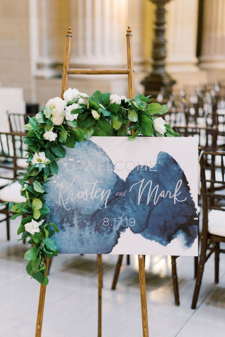 A welcome sign with an absract watercolor background the shade of Classic Blue: Color Of The Year