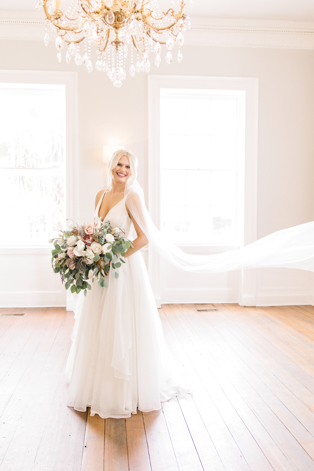 Smiling Bride Holding Overflowing Bouquet