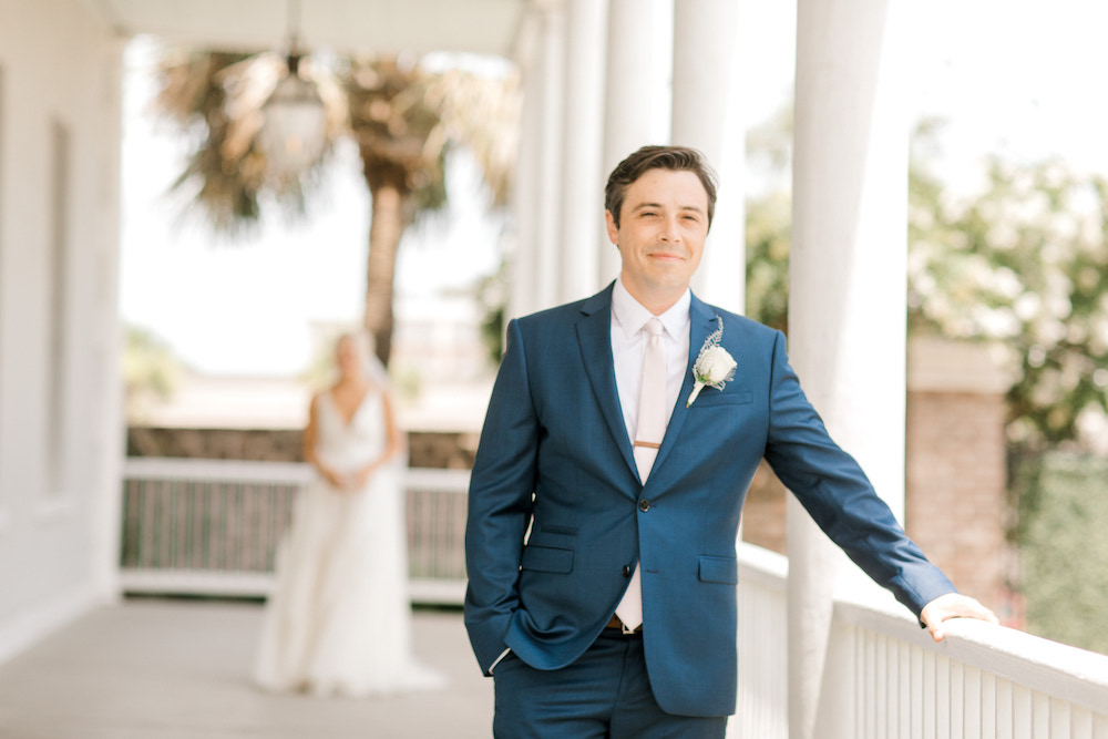 Groom with bride out of focus behind him