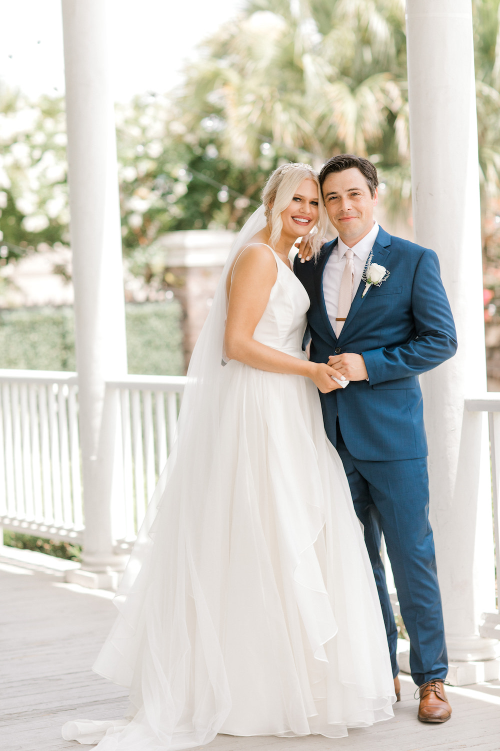 Bride and groom smiling on a classic southern porch