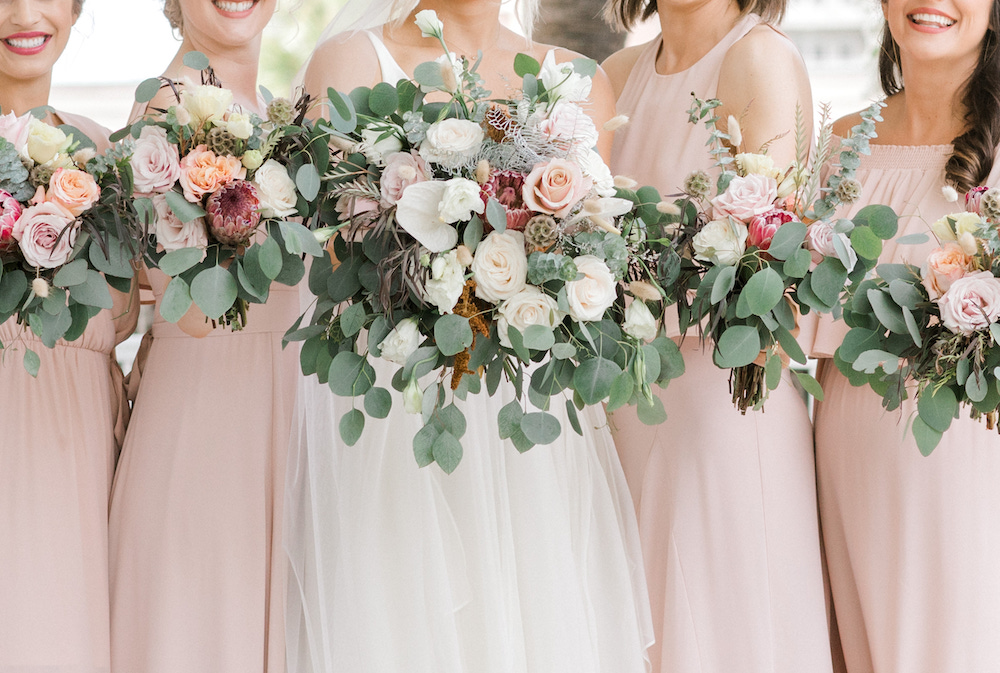 Bridal party holding out their bouquets