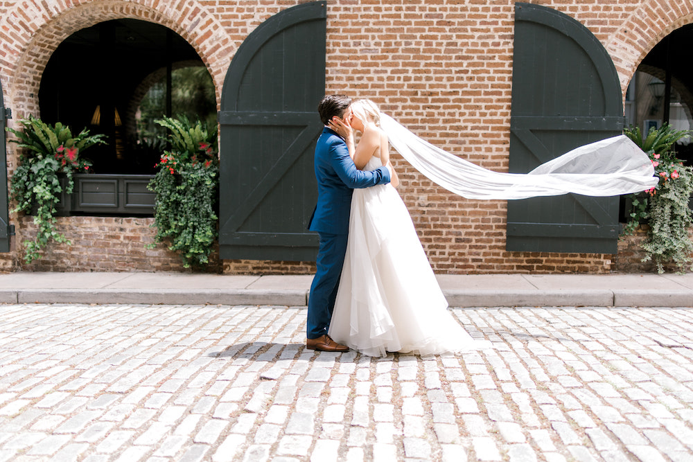Groom and bride kissing with beil flying behind