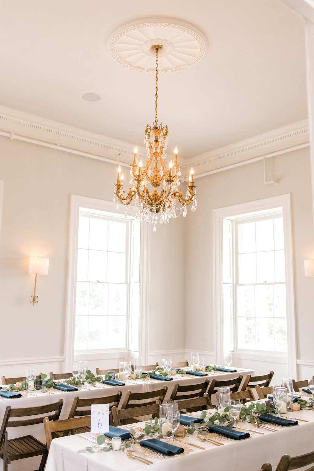 Classic chandelier over simple table settings